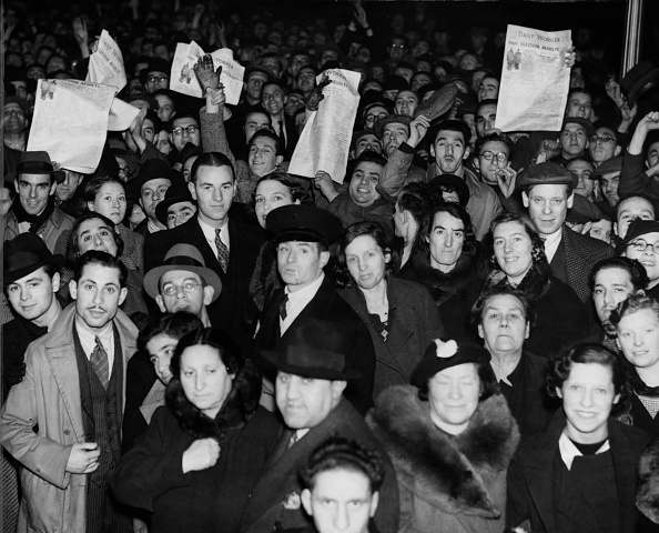 People holding copies of the Communist publication the 'Daily Worker' in Hackney, London, following the news of a Labour Party win in Bow and Bromley in the General Election, 14th November 1935.