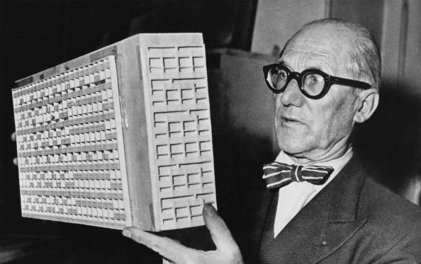 Swiss-born French architect and designer Le Corbusier (Charles-Edouard Jeanneret, 1887 - 1965) holding an architectural model of a high-rise building, circa 1950.