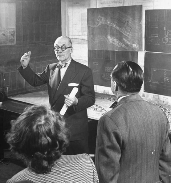 Architect Ernest Cormier (R) listening as fellow architect Le Corbusier (C) discusses design for the United Nations headquarters buildings.