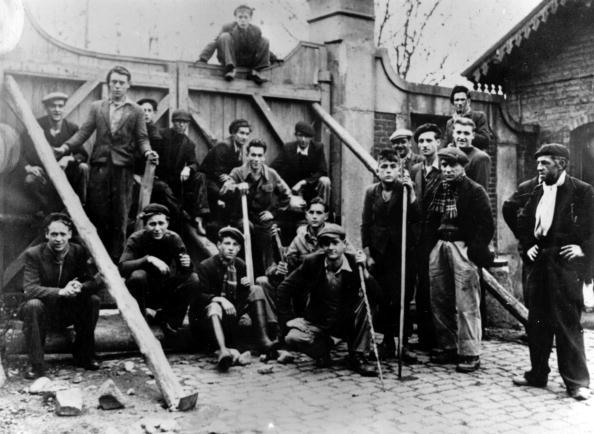 October 1948: In the St Etienne region miners at a barricaded door to prevent security troops from approaching coal-pits. About 100 aeroplane-loads of troops from North Africa have been flown in to supplement the 10,000 soldiers already guarding pits against Communist saboteurs.