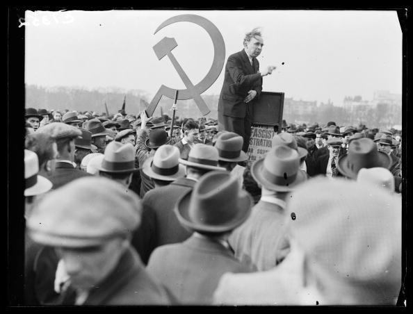Protest meeting, Hyde Park, London, 1933. A photograph of a crowd of Jewish protestors and sympathisers meeting in Hyde Park, London, taken by Tomlin for the Daily Herald newspaper on 2 April, 1933. This man is speaking to a crowd gathered to protest against the rising tide of anti-semitism in Nazi Germany. The large hammer and sickle in the background is carried by a group of Communist supporters. By 1933 the Nazis were directing a campaign of organised violence against Jews, their synagogues, businesses and property. This photograph has been selected from the Daily Herald Archive, a collection of over three million photographs. The archive holds work of international, national and local importance by both staff and agency photographers.