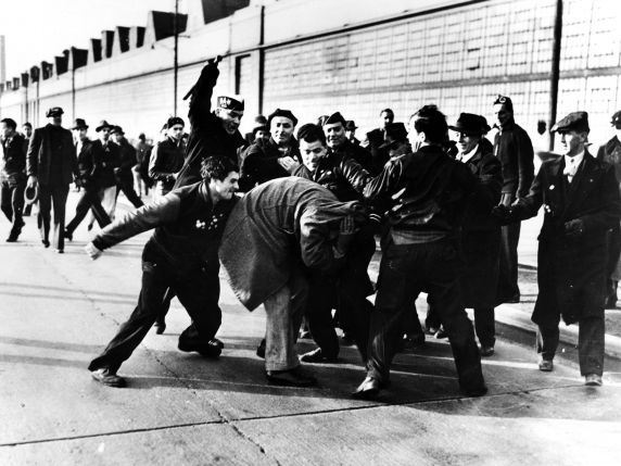 Striking auto workers beat a worker as he tries to cross the picket line during a 1941 strike at the Ford Rouge Plant, in Dearborn, Michigan.