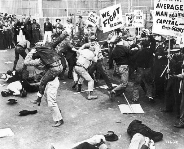 1935:  A scene depicting unionized strikers fighting with a group of 'scabs' or nonunion replacement employees as they try to cross the picket line at a factory. One of the strikers' signs reads 'We fight fascism.' Several men lay unconscious on the ground.