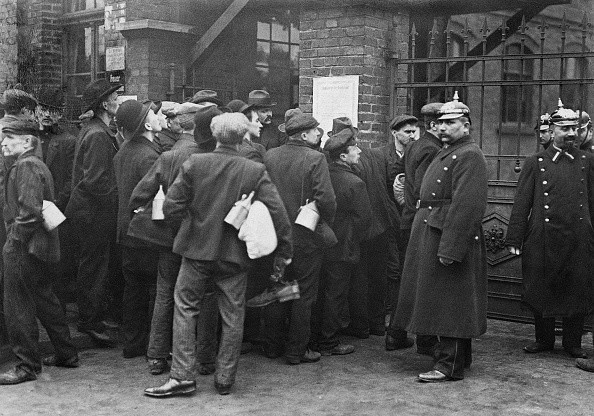 Striking miners at the river Ruhr: Strikers reading an enactment by the district president at the gate of the coal-mine that permits police the early use of firearms - March 1912