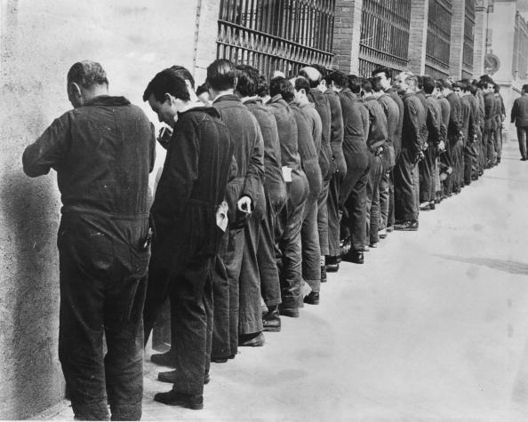 Factory workers in Spain, where striking is forbidden by law, protest by spending their lunch break standing facing the factory wall.  1968