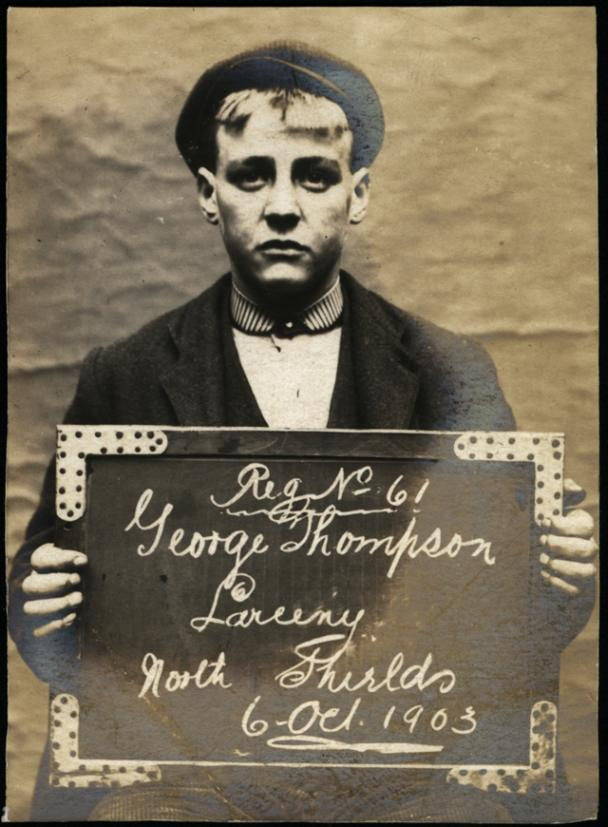 """Name: George Thompson Arrested for: Larceny Arrested at: North Shields Police Station Arrested on: 6 October 1903 Tyne and Wear Archives ref: DX1388-1-21-George Thompson   For an image of one his accomplices see www.flickr.com/photos/twm_news/18050615063/in/photostream/.   The Shields Daily Gazette for 6 October 1903 reports:   """"PILFERING FROM A NO. SHIELDS STORE   At North Shields to-day, George Thompson (17), cartman, Bedford Lane; James W. Brown (18), storeman, Upper Queen Street; John Fatherley (16), cartman, Old Fold; William Stott (15), cartman, Dotwick Street; and James Maine (25), cartman, Queen Street, were charged on remand with stealing from Mr George Otto's ship chandler's store in Borough Road, between Aug. 1st and Sept. 28th, five tins of butter, a shoulder of bacon, and a bottle of whisky, valued £2 3s 8d."""