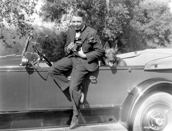 1925: George K Arthur, the stage name of G K A Brest ( 1899 - 1985 ) the diminutive but plucky British hero of the silent screen who later went to Hollywood and then became a financier and distributor of art shorts. Pictured sitting on the side of his sports car with his alsatian dog in the back, he is currently filming 'The Exquisite Sinner' for Metro_Goldwyn-Mayer. (Photo by Margaret Chute/Getty Images)