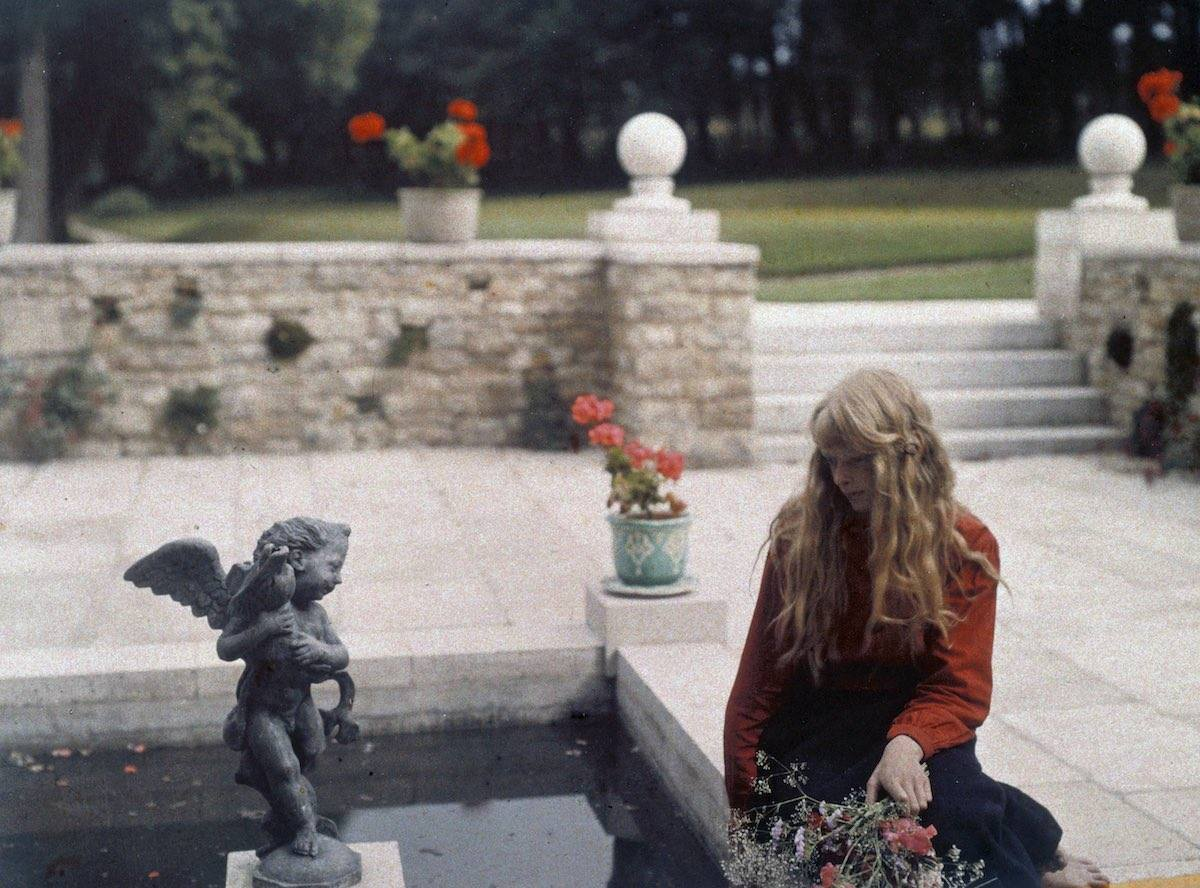 A portrait of Christina, gazing thoughtfully into an ornamental pond. The location for this photograph is not known but may possibly be the gardens of Rempstone Hall near Corfe Castle in Dorset.