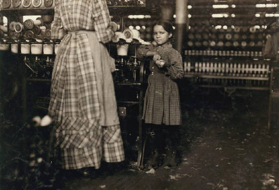 "Little Fannie, 7 years old, 48 inches high, helps sister in Elk Mills. Her sister (in photo) said, ""Yes, she he'ps me right smart. Not all day but all she can. Yes, she started with me at six this mornin'."" These two belong to a family of 19 children. Location: Fayetteville, Tennessee, November 1910, Lewis Hine."
