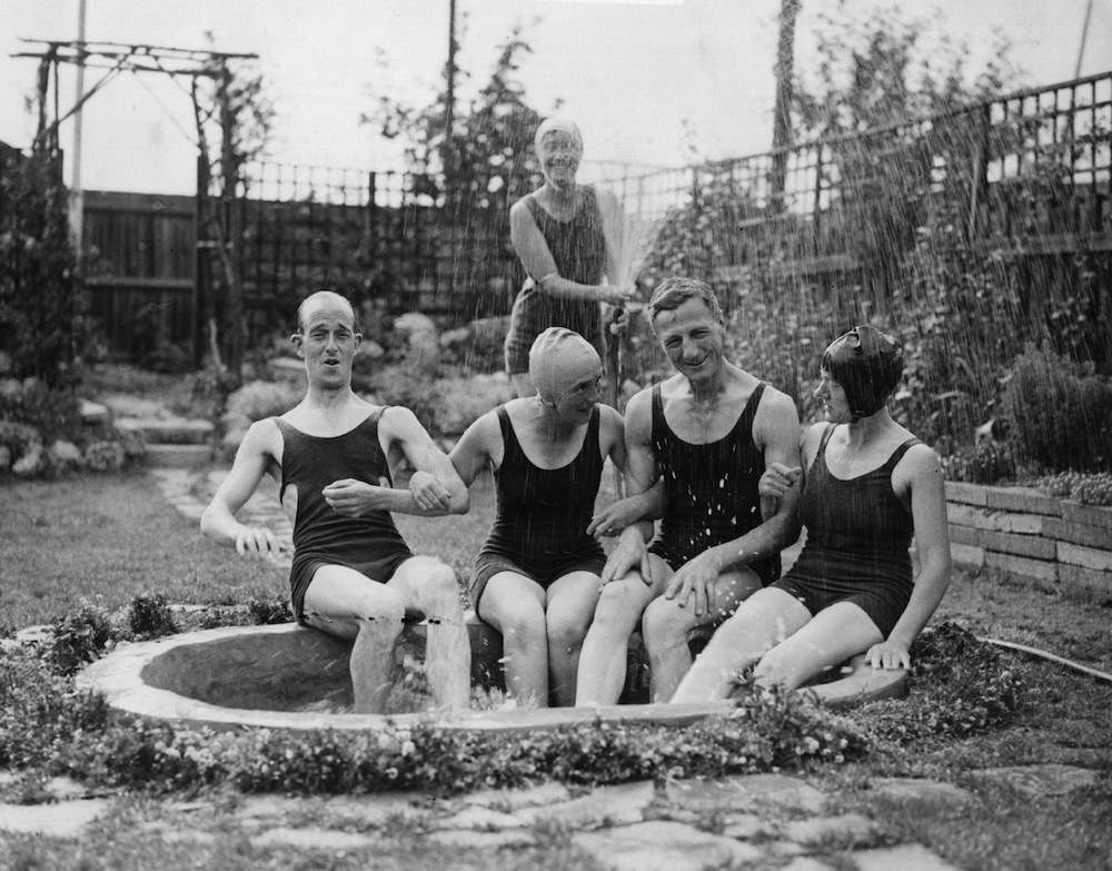 A group of people take refuge from the heatwave with a hose-pipe shower in their garden pond, Streatham, London.   (Photo by Fox Photos/Getty Images) August 26, 1933