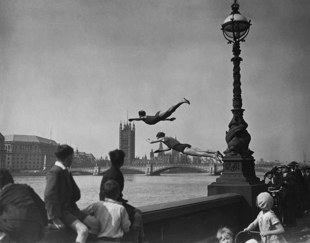 Two divers jumping off the Embankment into the River Thames in London, near Westminster Bridge.   (Photo by H F Davis/Getty Images) May 13, 1934