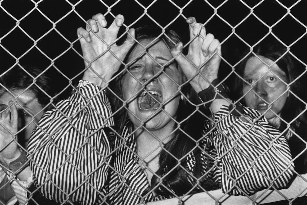 A hysterical fan grasps a wire fence at a David Cassidy concert at White City, West London.