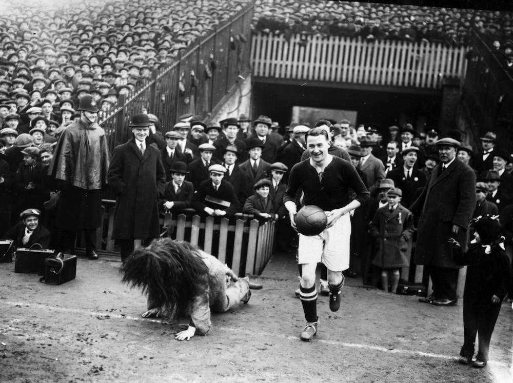 Millwall Football Club captain, Len Graham, fails to conceal his amusement as he leads his team out at the Den and the mascot, a man dressed as a lion, falls over.   (Photo by H F Davis/Getty Images)