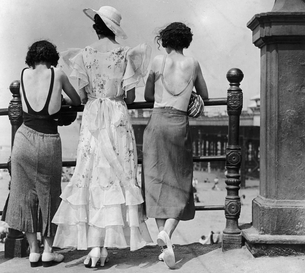 July 10, 1934. Three women on Blackpool promenade during a heatwave. One wears a divided skirt and the other a straight skirt, both over swimwear. The middle one has a 'copy' of the Letty Lynton dress made popular by Joan Crawford in the film of that name. Adapted for the mass market the triple row of frills at the hem are matched by frills at the shoulder forming cap sleeves.   (Photo by E  Dean/Getty Images)