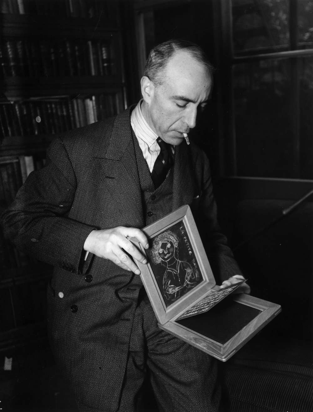 1932:  Harry Price, Director of the National Society of Psychical Research showing how 'spirit' writing  can be done between two apparently sealed slates.  (Photo by General Photographic Agency/Getty Images)