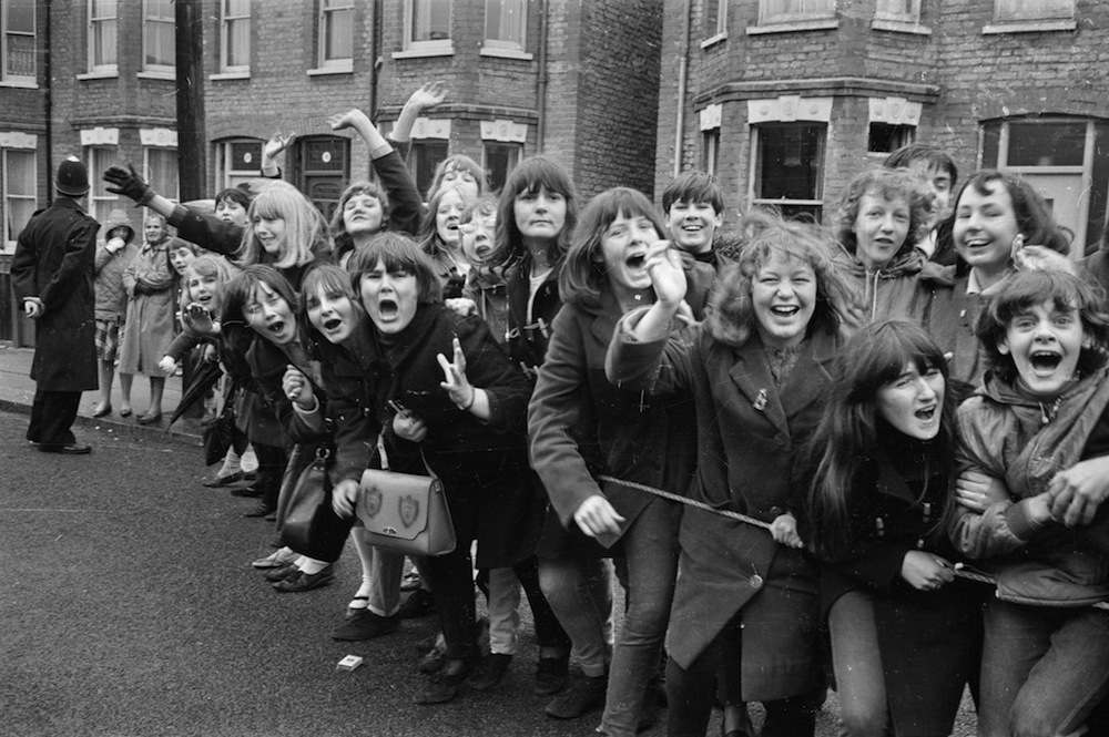 15th March 1965:  British police hold back excited young Beatles fans hoping for a glimpse of their musical heroes during the filming of the musical 'Help', on location in London.  (Photo by Stan Meagher/Express/Getty Images)