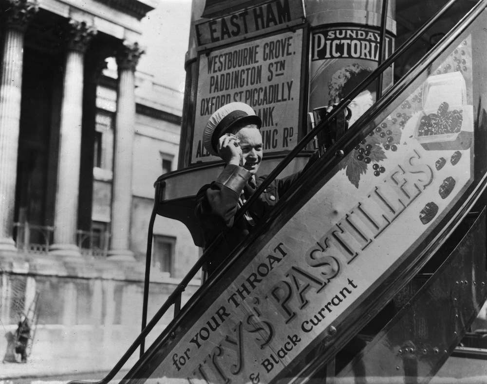 19th August 1932:  A bus conductor wipes the sweat from his face as he climbs the stairs to collect fares from the top deck of his bus in Trafalgar Square during a heat wave.  (Photo by A. Hudson/Topical Press Agency/Getty Images)