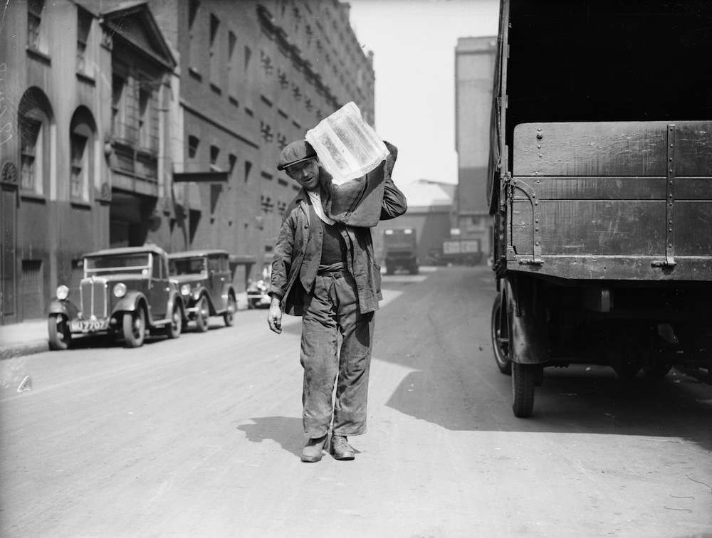 June 1936:  A worker distributing blocks of ice for the Pure Ice company during a heatwave.  (Photo by Fox Photos/Getty Images)