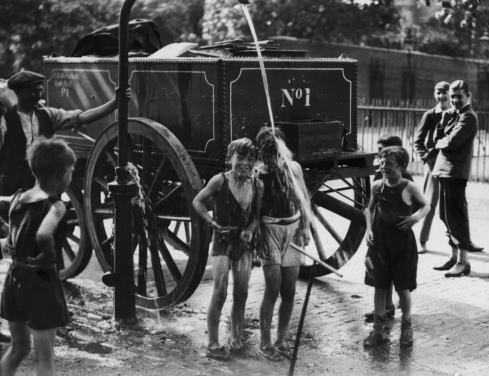 August 1930:  A water cart man turns the water main on a group of boys to help them cool off in a street in Westminster, London during a heatwave.  (Photo by Fox Photos/Getty Images)