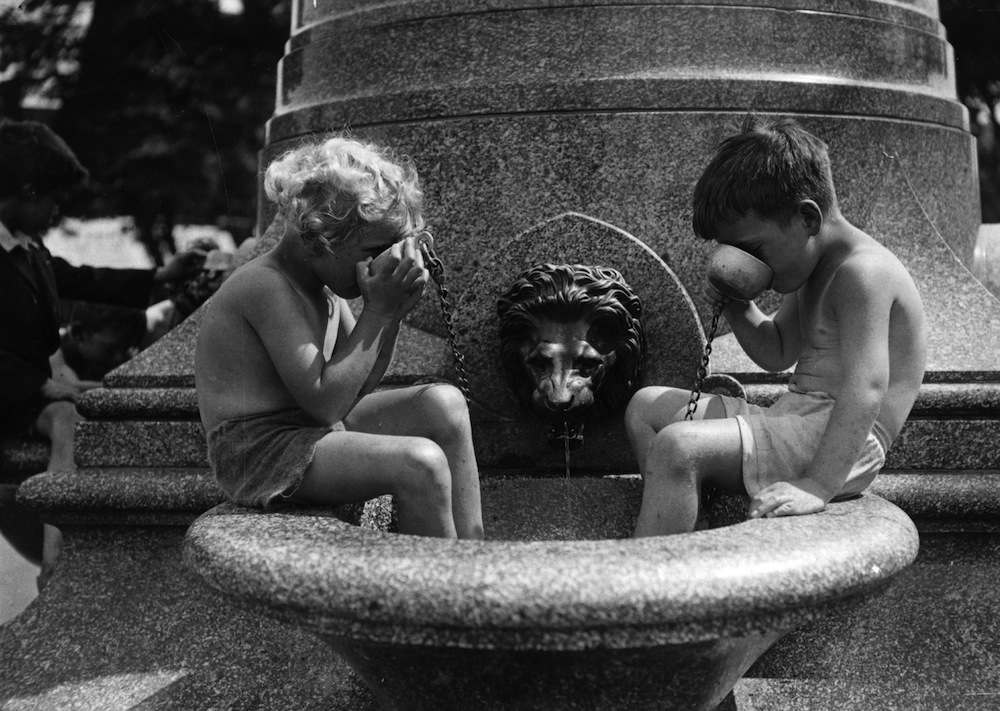 6th August 1937:  Children enjoy a cooling drink from the fountain on Clapham Common.  (Photo by H. Allen/Topical Press Agency/Getty Images)
