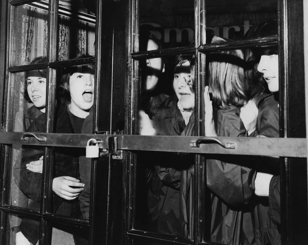 4th November 1963:  A group of girls bang and shout at the door of the Prince of Wales Theatre in London's West End, where The Beatles are rehearsing for the Royal Command Performance.  (Photo by B. Marshall/Fox Photos/Getty Images)