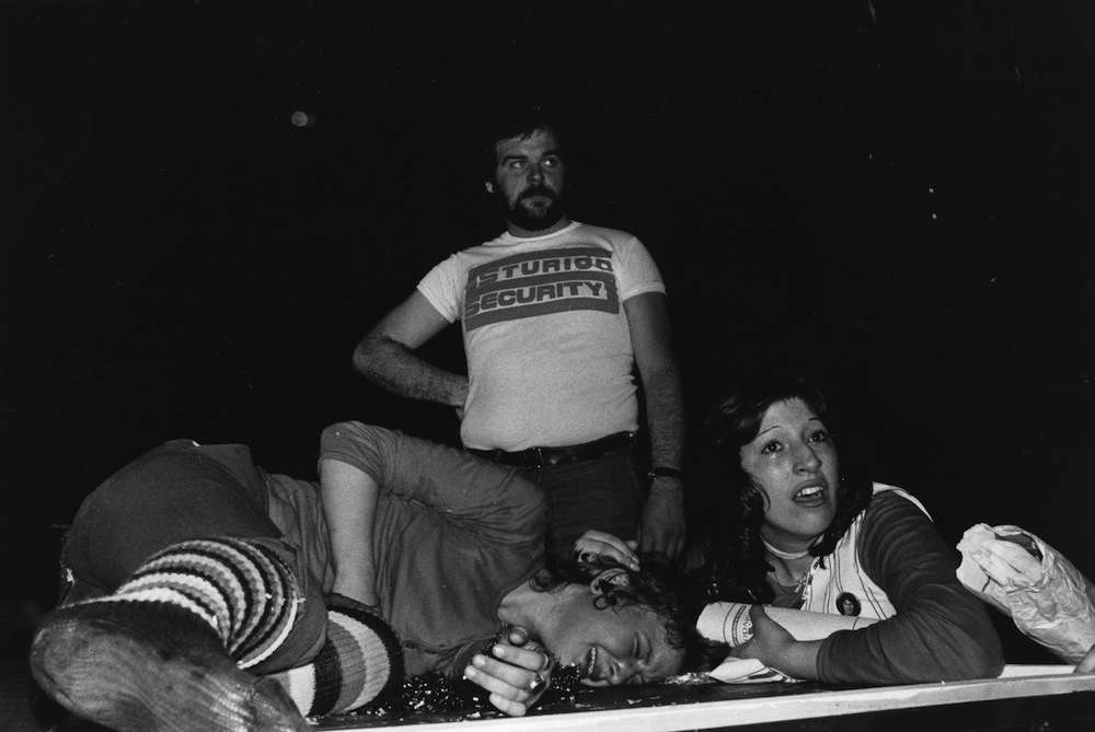 17th May 1974:  A young fan lies crying on the stage of the Hammersmith Odeon, London, comforted by a friend, at a concert by the British rock group Slade. A security guard stands behind.  (Photo by Graham Wood/Evening Standard/Getty Images)