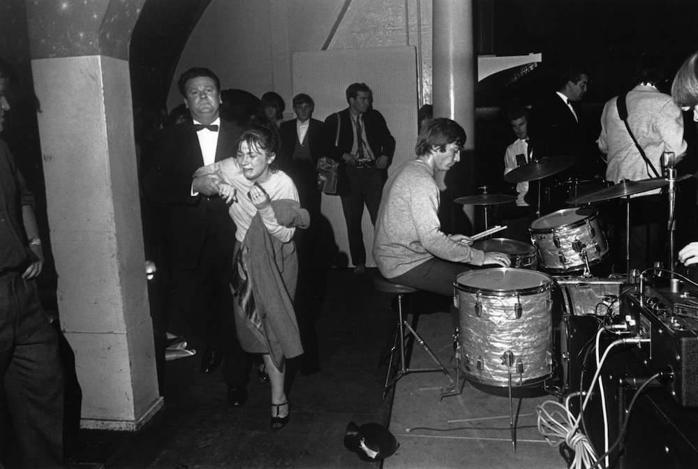 14th August 1964:  A tearful fan is escorted off the stage as pop group The Rolling Stones perform at the Wimbledon Palais, London. Drummer Charlie Watts is in the centre.  (Photo by Davies/Express/Getty Images)