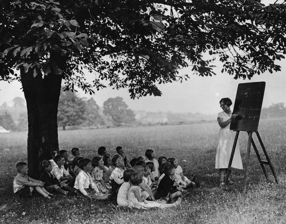 27th July 1935:  Pupils have a lesson in the open air in the shade of a tree at Winterbourne, Gloucestershire, during a spell of hot weather.  (Photo by Fox Photos/Getty Images)