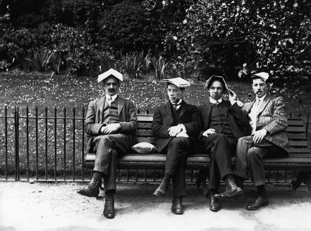 1st July 1913:  Men cover their heads with newspapers to protect them from the summer sun.  (Photo by Topical Press Agency/Getty Images)