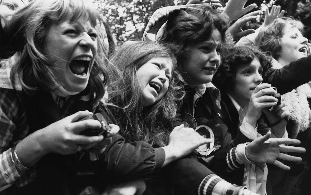 30th May 1975:  A crowd of over-excited teenage girls scream and cry at the sight of their idols, pop group The Osmonds.  (Photo by Evening Standard/Getty Images)