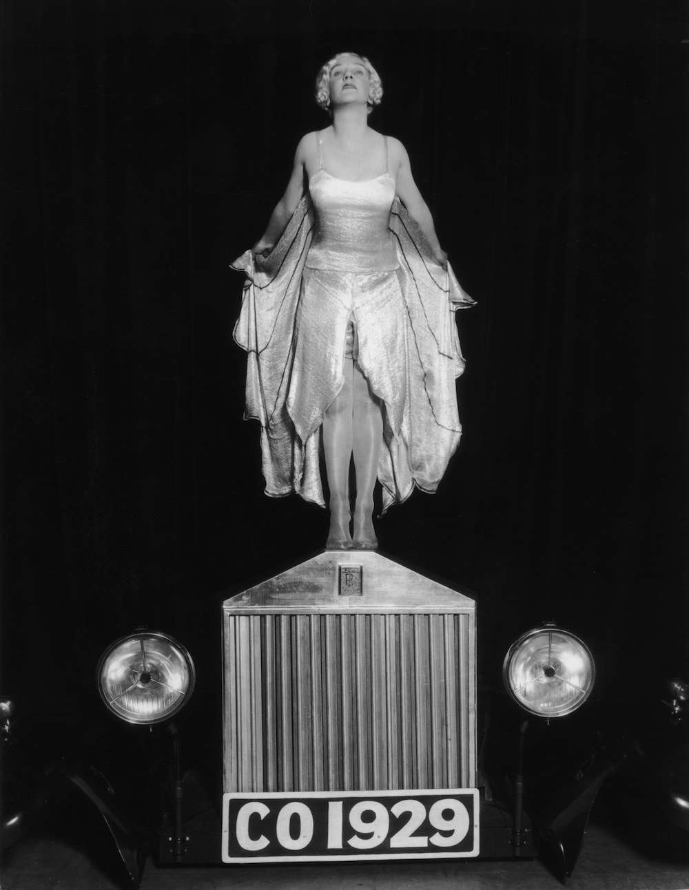 1929:  Entertainer Elsa McFarlane stands on the bonnet of a Rolls Royce car, mimicking the Silver Lady figurine, in a production of 'The Co-Optimists', at the Vaudeville Theatre in London.  (Photo by Sasha/Getty Images)
