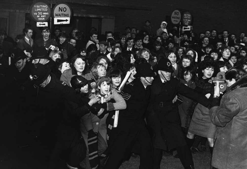 1964:  Policemen struggle to control an excited crowd of young female Beatles fans.  (Photo by Keystone/Getty Images)