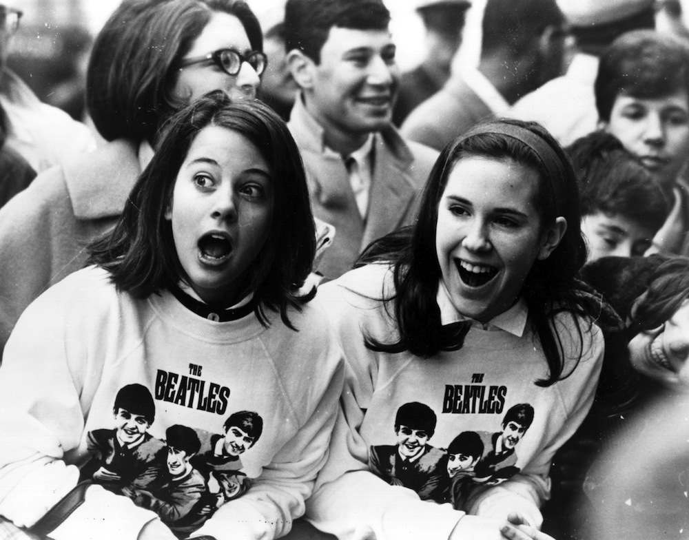 10th February 1964:  Two excited girls in Beatles sweatshirts, amongst a crowd of fans in New York, welcoming the group as they arrive at the airport.  (Photo by Keystone/Getty Images)