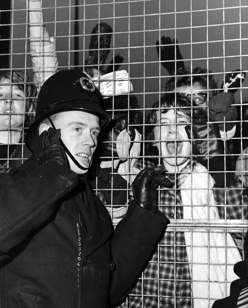 22nd February 1964:  A London policeman has to block his ears as a crowd of Beatles fans give the Fab Four their typical welcome at London Airport, after their tour of USA.  (Photo by Fox Photos/Getty Images)