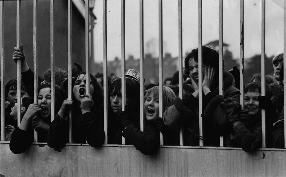 24th February 1964:  A group of Beatles fans waiting for a glimpse of their idols outside ABC Television Studios in Teddington, where they are working on a new film. This group of fans had waited three hours in the rain, only to be told that the Beatles would not be leaving for at least another eight hours, undeterred, they decided to stay and wait.  (Photo by Keystone/Getty Images)