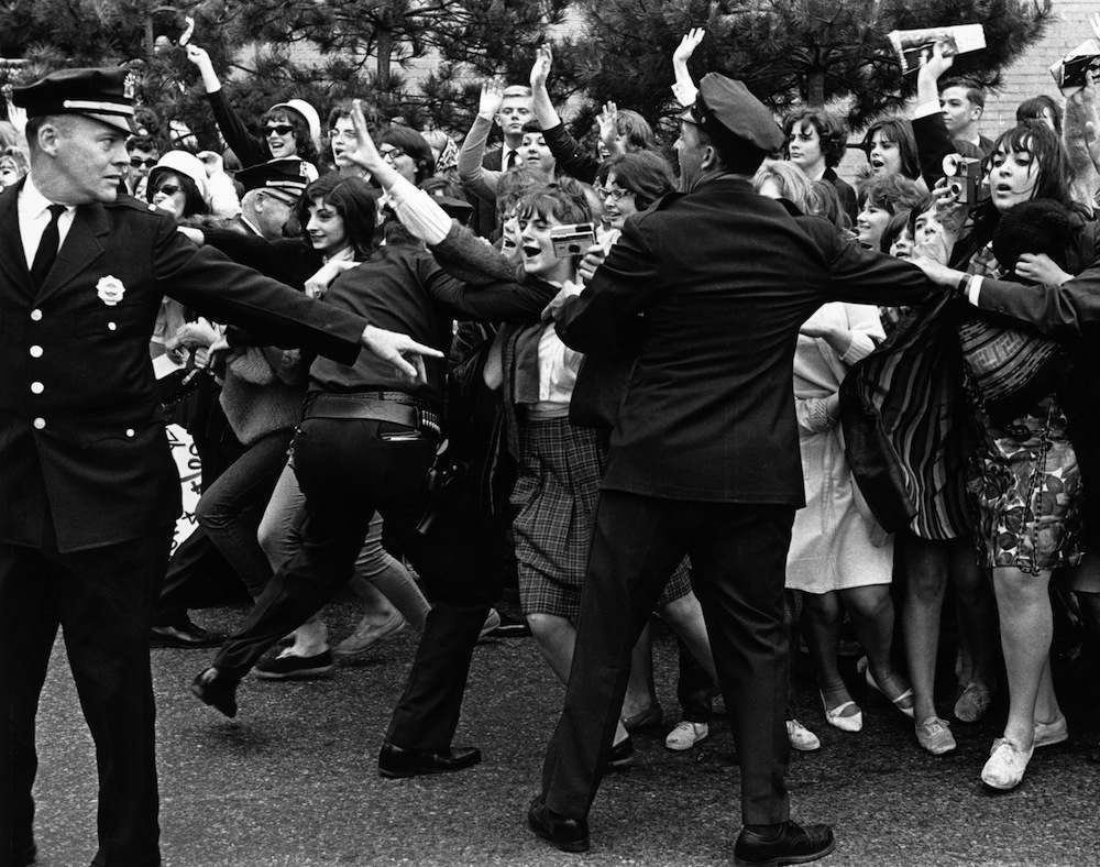 June 1964:  American policemen holding back Rolling Stones fans in New York.  (Photo by William Lovelace/Express/Getty Images)