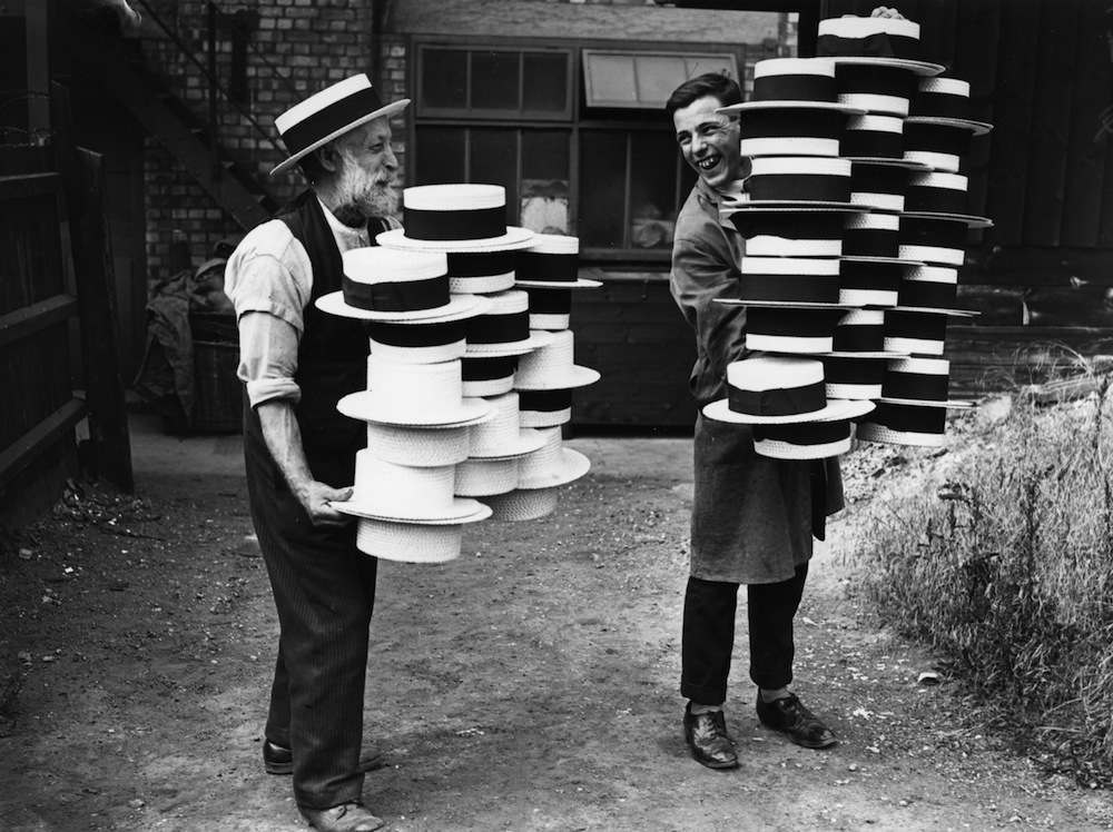 circa 1928:  Workers at a hat manufacturers in Luton carrying piles of men's straw hats, which were in demand due to a heatwave.  (Photo by Topical Press Agency/Getty Images)