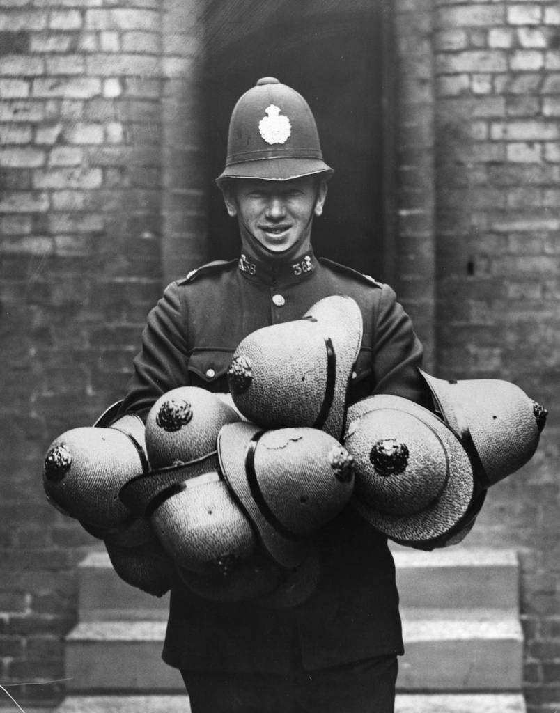 circa 1935:  A policeman carrying a consignment of straw helmets at Luton Police Station. The straw version replaces the standard blue helmet in a bid to beat the hot weather.  (Photo by Fox Photos/Getty Images)