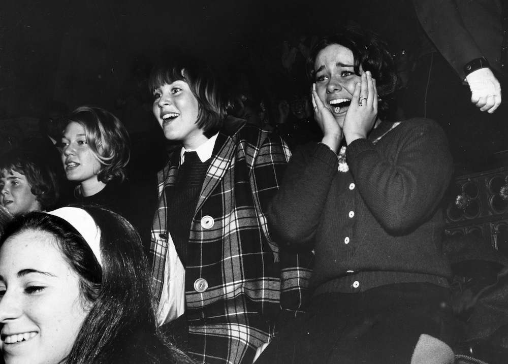 10th February 1964:  A group of Beatles fans watching their heroes perform on the American television programme 'The Ed Sullivan Show'.  (Photo by Central Press/Getty Images)