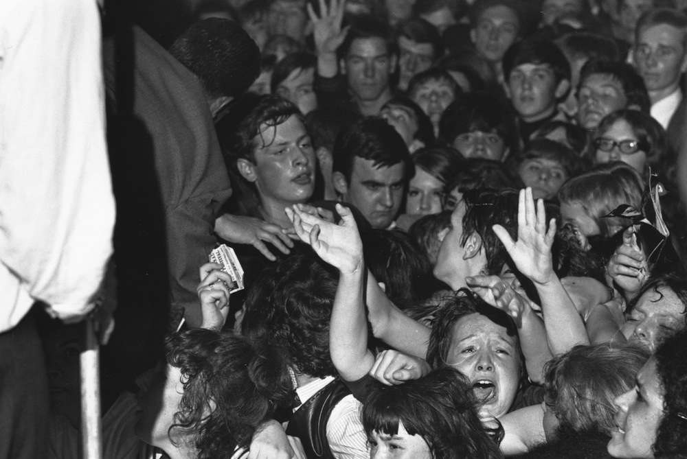 14th August 1964:  Fans watching the Rolling Stones in concert at the Wimbledon Palais, London. For some the excitement verges on hysteria.  (Photo by Davies/Express/Getty Images)