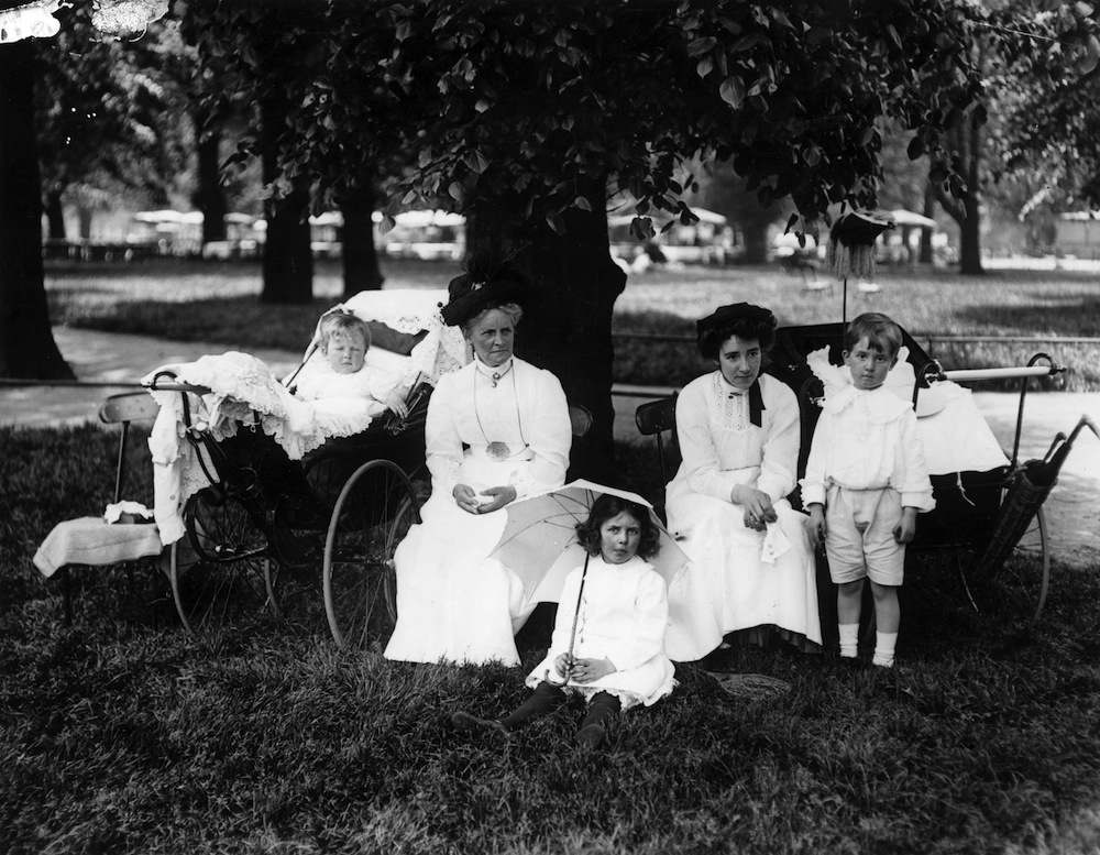 1913:  Nannies with their charges under a tree in Kensington Gardens, London, during a heatwave.  (Photo by Topical Press Agency/Getty Images)