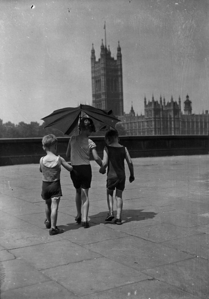 25th June 1935:  Three little boys shelter from the sun under a battered umbrella during London's summer heatwave.  (Photo by E. Dean/Topical Press Agency/Getty Images)