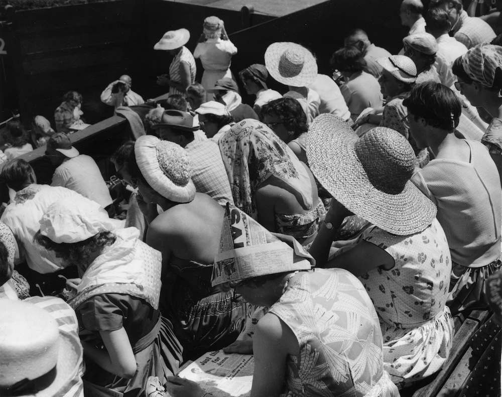 29th June 1957:  Spectators shading themselves from the sun at the Wimbledon tennis tournament, during a heatwave in London.  (Photo by Keystone/Getty Images)