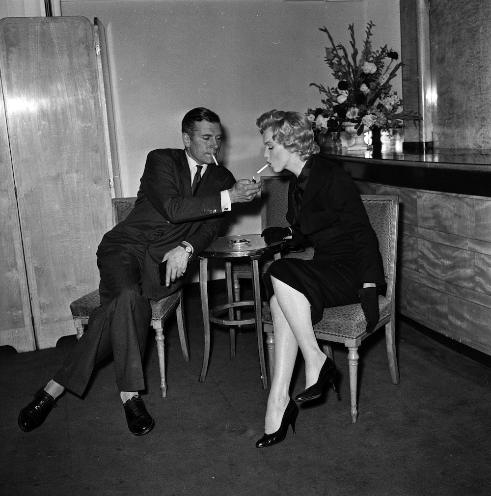 17th July 1956:  American film star Marilyn Monroe (1926 - 1962) accepts a light from British thespian Laurence Olivier (1907 - 1989) at a press conference at the Savoy Hotel, London.  (Photo by Harry Kerr/BIPs/Getty Images)