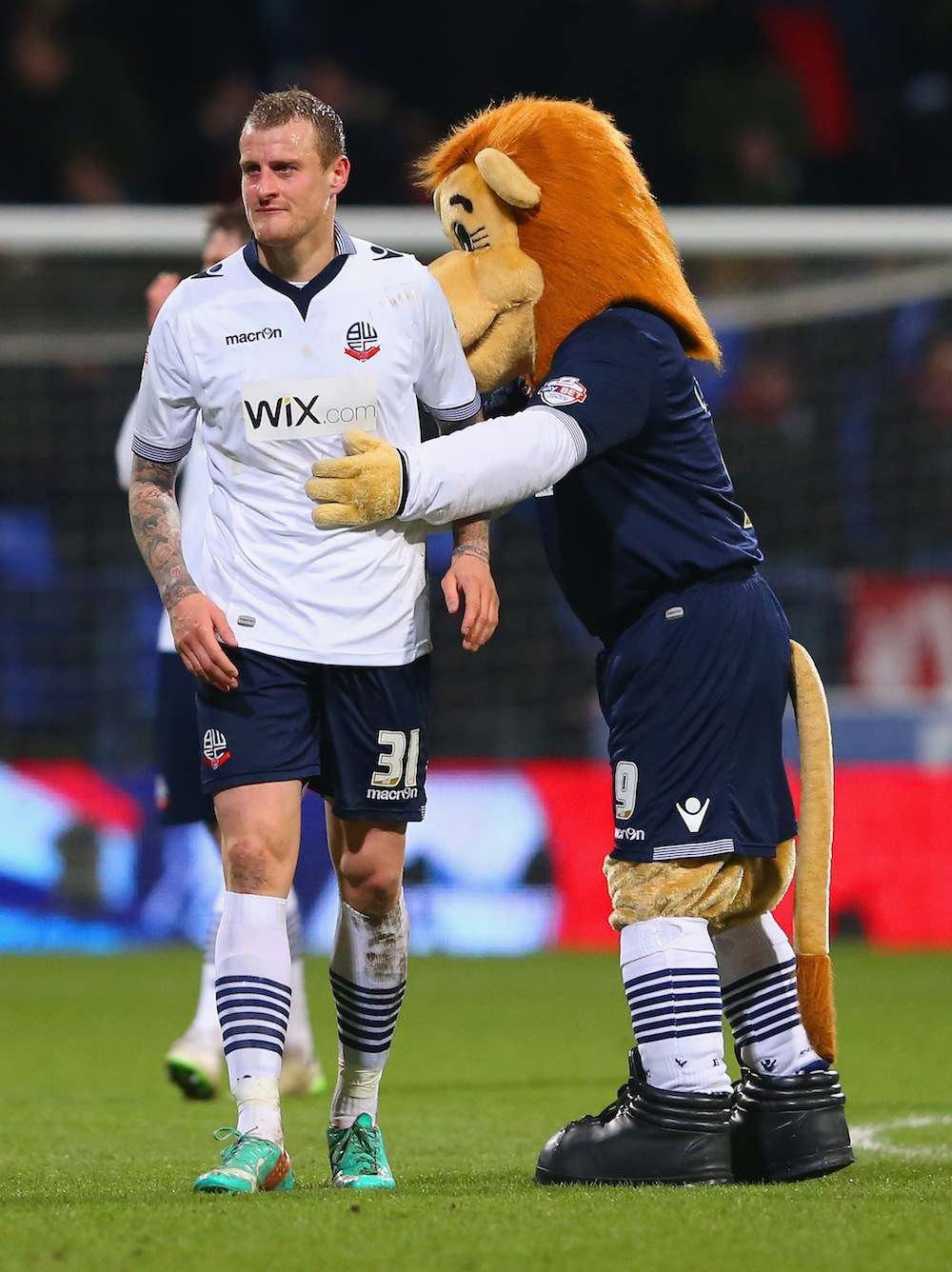 BOLTON, ENGLAND - FEBRUARY 04:  Lofty the Lion mascot consoles David Wheater of Bolton Wanderers after defeat in the FA Cup Fourth round replay between Bolton Wanderers and Liverpool at Macron Stadium on February 4, 2015 in Bolton, England.  (Photo by Alex Livesey/Getty Images)