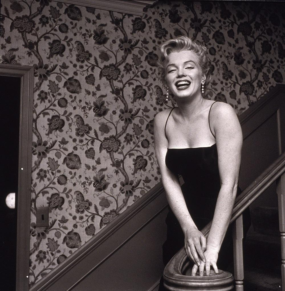 American actress Marilyn Monroe (1926 - 1962) stands in a staircase alongside a wall with a floral-motif pattern, late 1950s. She wears a black cocktail dress and dangling earrings. (Photo by Hulton Archive/Getty Images) 1959