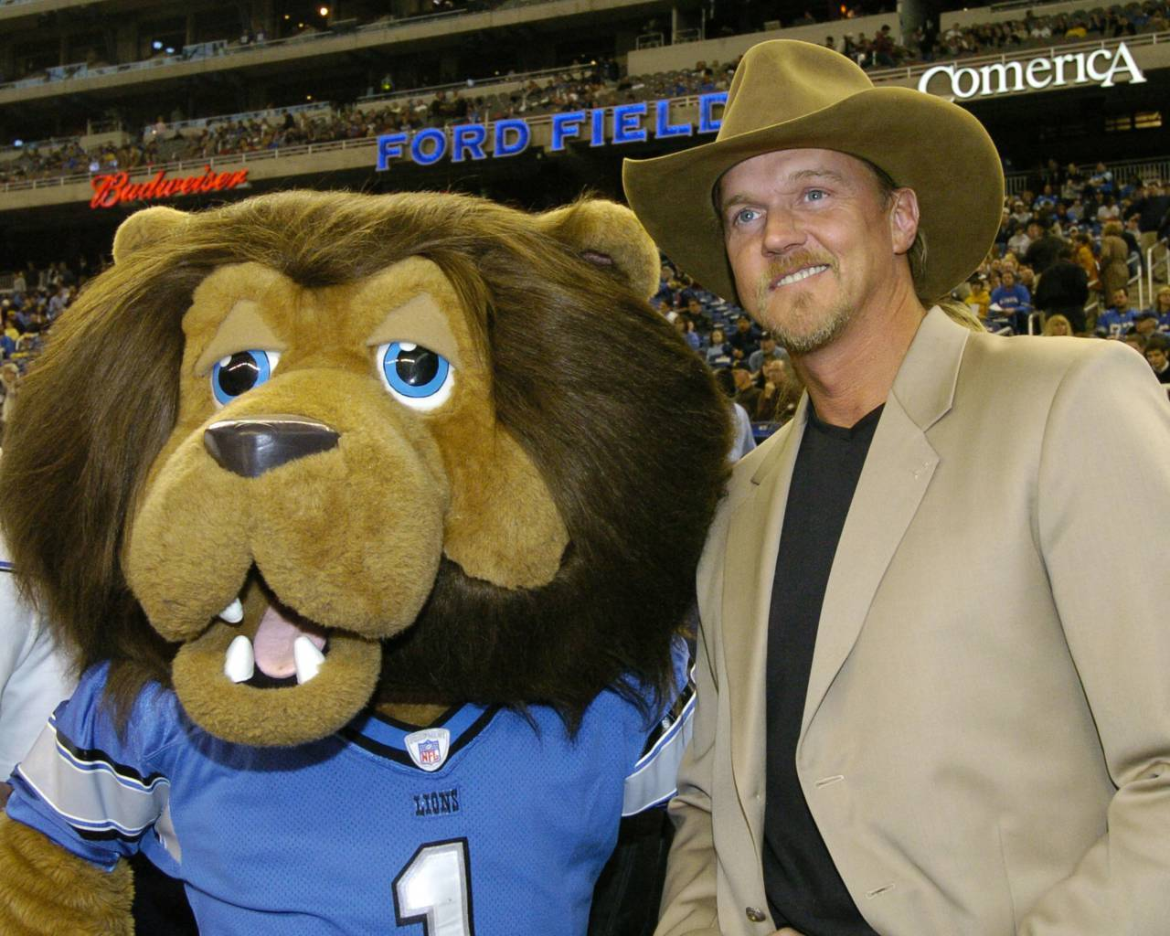 Trace Adkins poses the Detroit Lions mascot before sining the national anthem at a Thanksgiving Day game, November 25, 2005, in Detroit. (Photo by Al Messerschmidt/Getty Images)