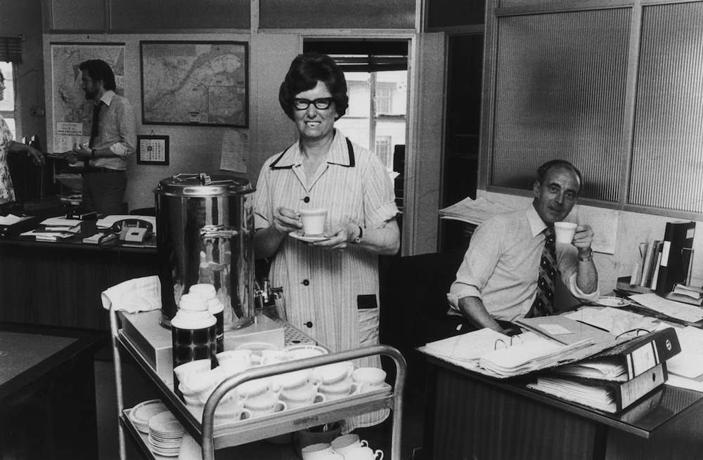 Tea lady Alice Bond providing refreshments for office workers, 13th July 1976. (Photo by M. Fresco/Evening Standard/Hulton Archive/Getty Images)