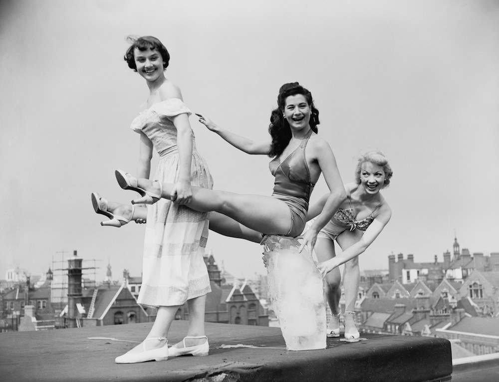 Chorus girls from the show 'Sauce Tartare' at the Cambridge Theatre in London, keep cool on the roof of the theatre with a block of ice, 28th June 1949. From left to right, they are Audrey Hepburn (1929 - 1993), Enid Smeedon and Aud Johanssen of Norway. (Photo by Ron Case/Keystone/Hulton Archive/Getty Images)