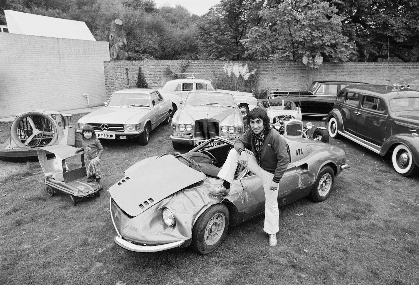 Drummer Keith Moon (1947 - 1978), of British rock group The Who at Tara, his home in Chersey, Surrey, with his daughter, Amanda (left), and some of the cars in his collection, 17th October 1972. Moon is sitting on a damaged Ferrari Dino. (Photo by Jack Kay/Daily Express/Hulton Archive/Getty Images)